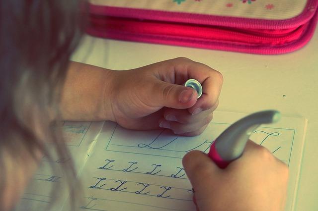Dziecko pisze litery w zeszycie