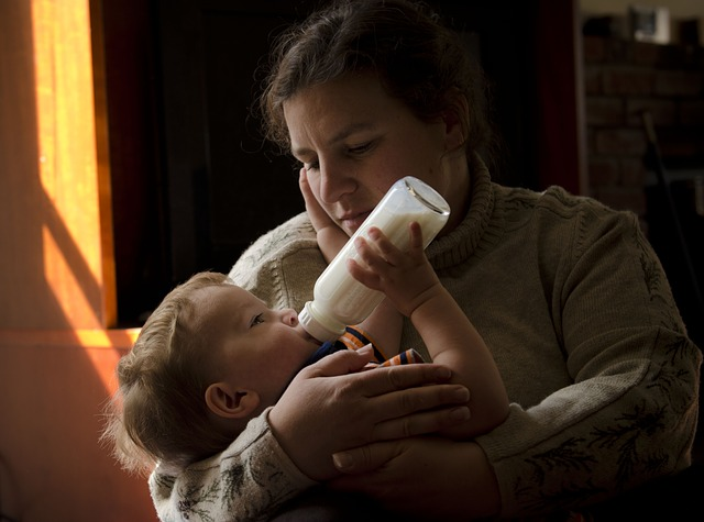 Kobieta karmi dziecko butelką